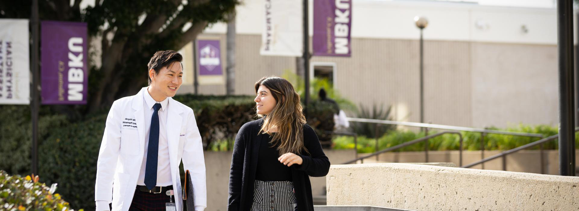Male student wearing a white coat chats with female student at the Fullerton campus
